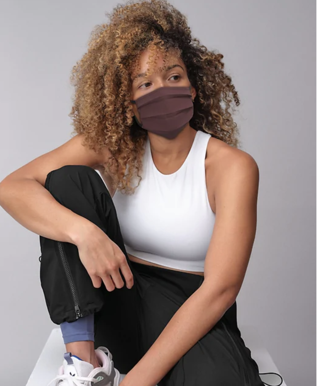 A model in athletic gear and a face mask