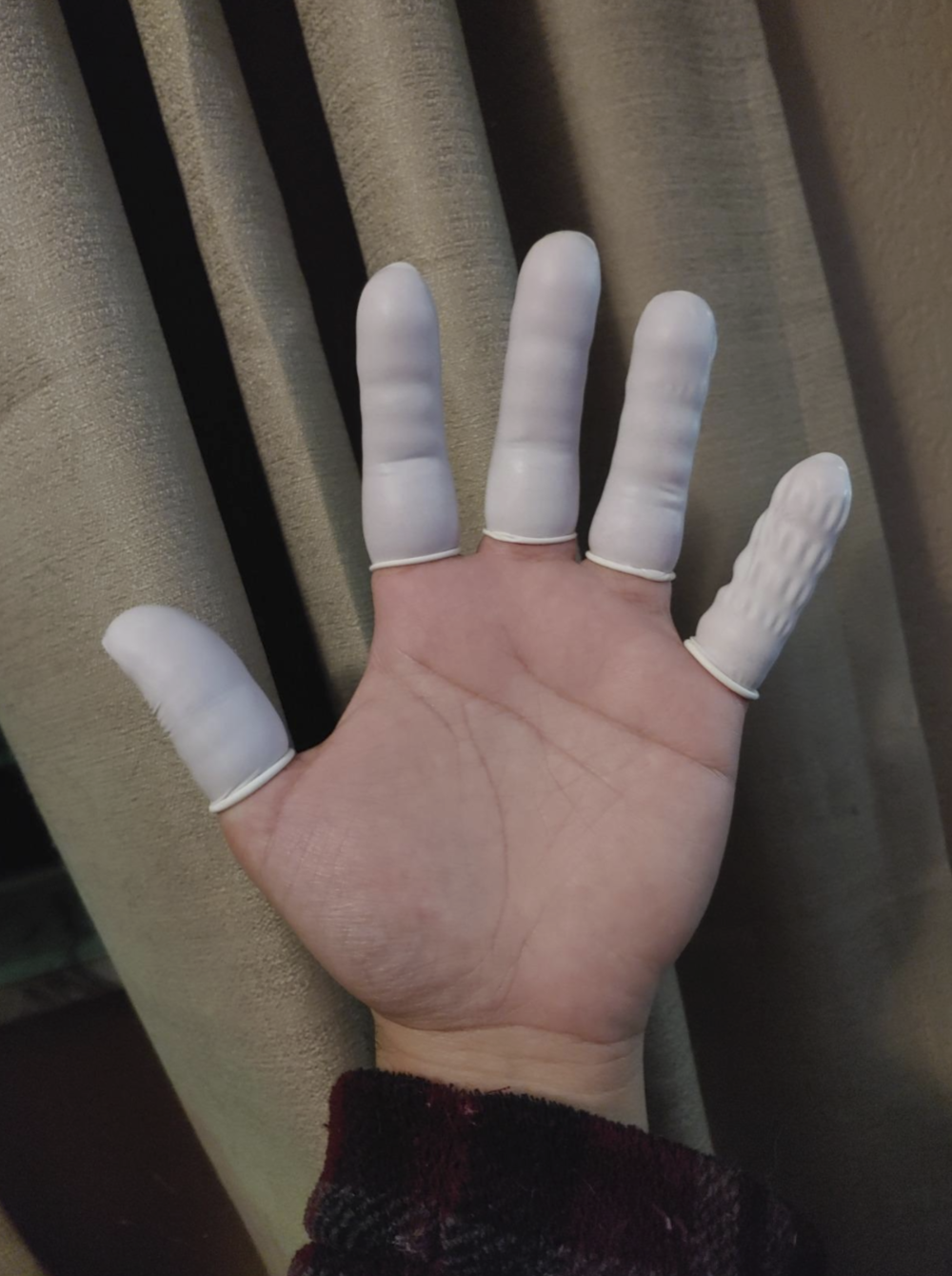 A reviewer's hand wearing individual latex covers for each finger