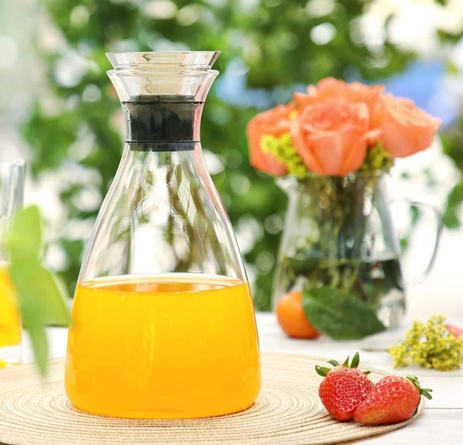 the clear carafe with orange juice inside