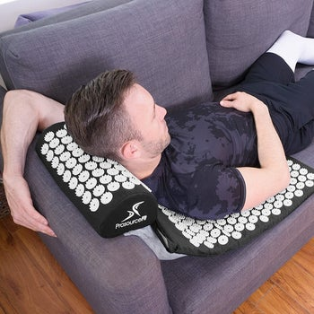 A person laying on top of the mat on their sofa, the mat pillow is raised on the edge of the armrest