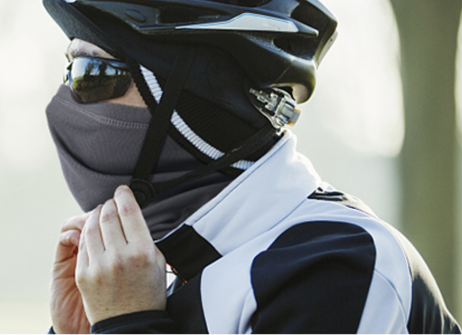A biker with a face covering that covers their nose, mouth, chin, and neck