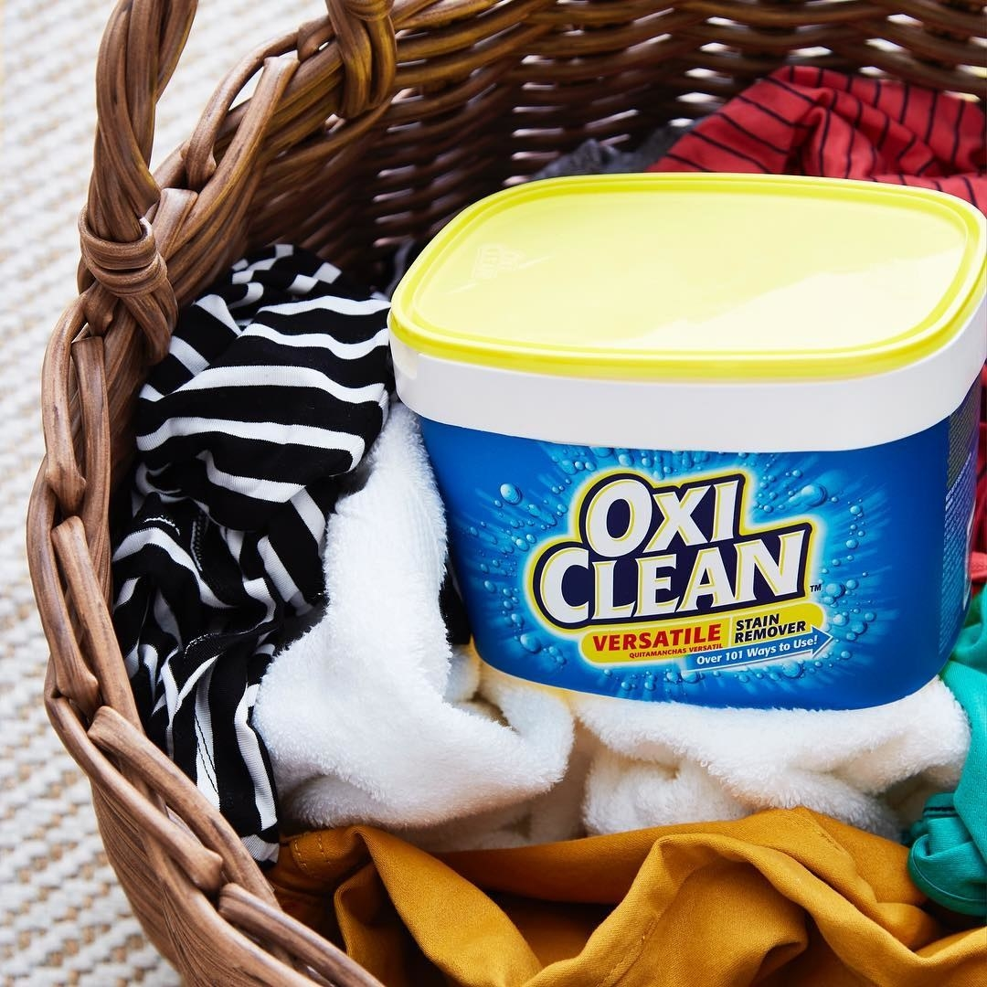 A tub of Oxi Clean stain remover sitting in a laundry basket full of clothes