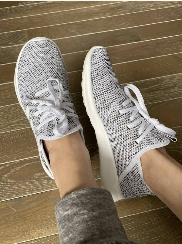 A reviewer in a pair of grey lace-up slip on sneakers