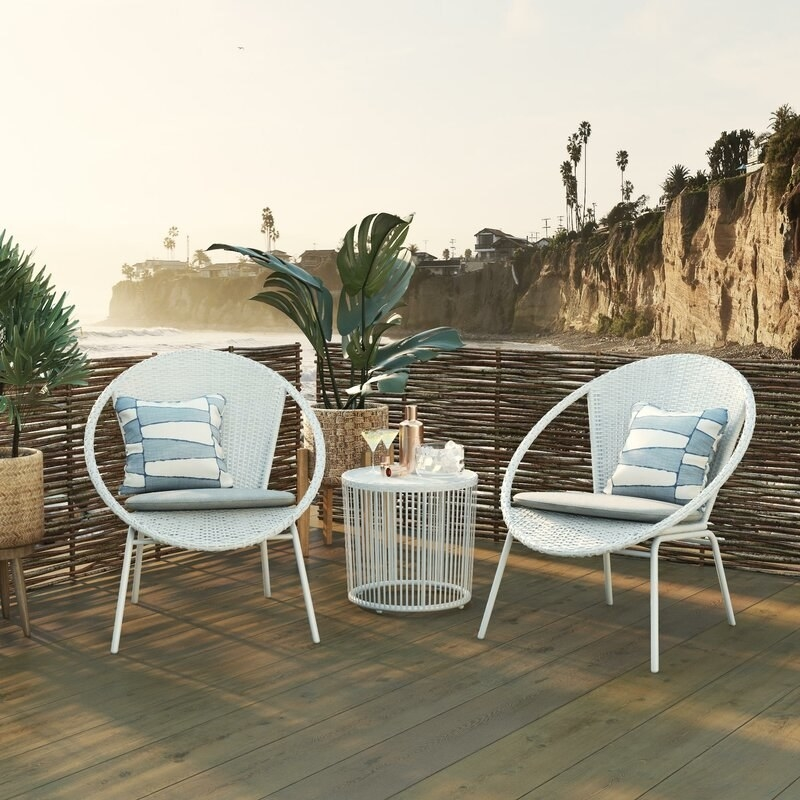 Two round, white wicker chairs with a side table