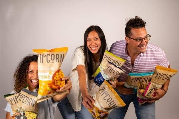 Pipcorn founders hold up all the bags of cheese balls
