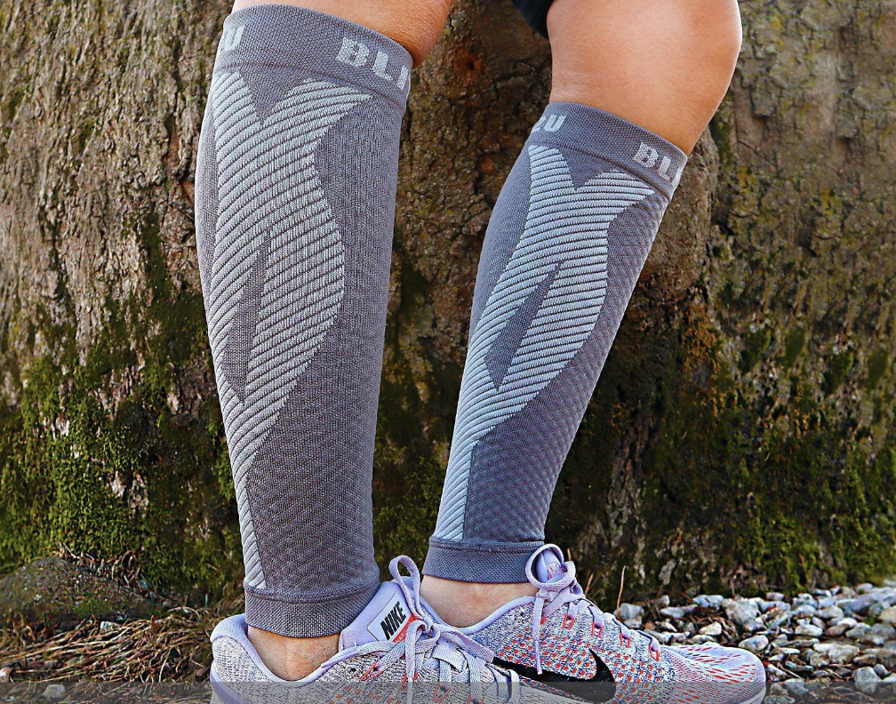 A model in gray compression sleeves that go from the bottom of the knee to the ankle