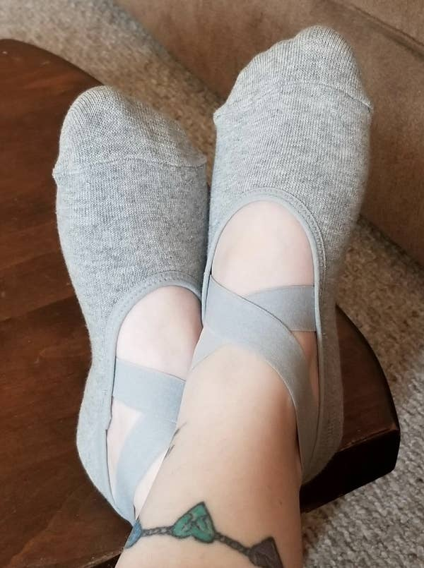 A reviewer image of feet wearing the gray socks with two crossover elastic straps on the top of the foot