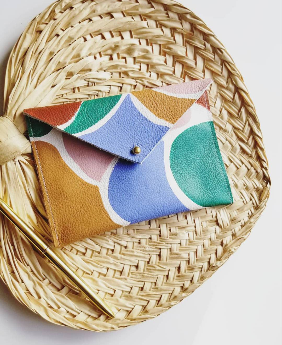 Multi-colored geometric money pouch against straw surface