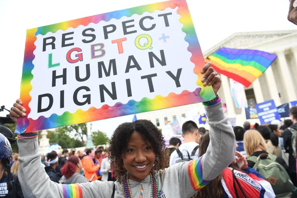 """Person holding up rainbow sign that reads, """"Respect LGBTQ+ Human Dignity"""""""