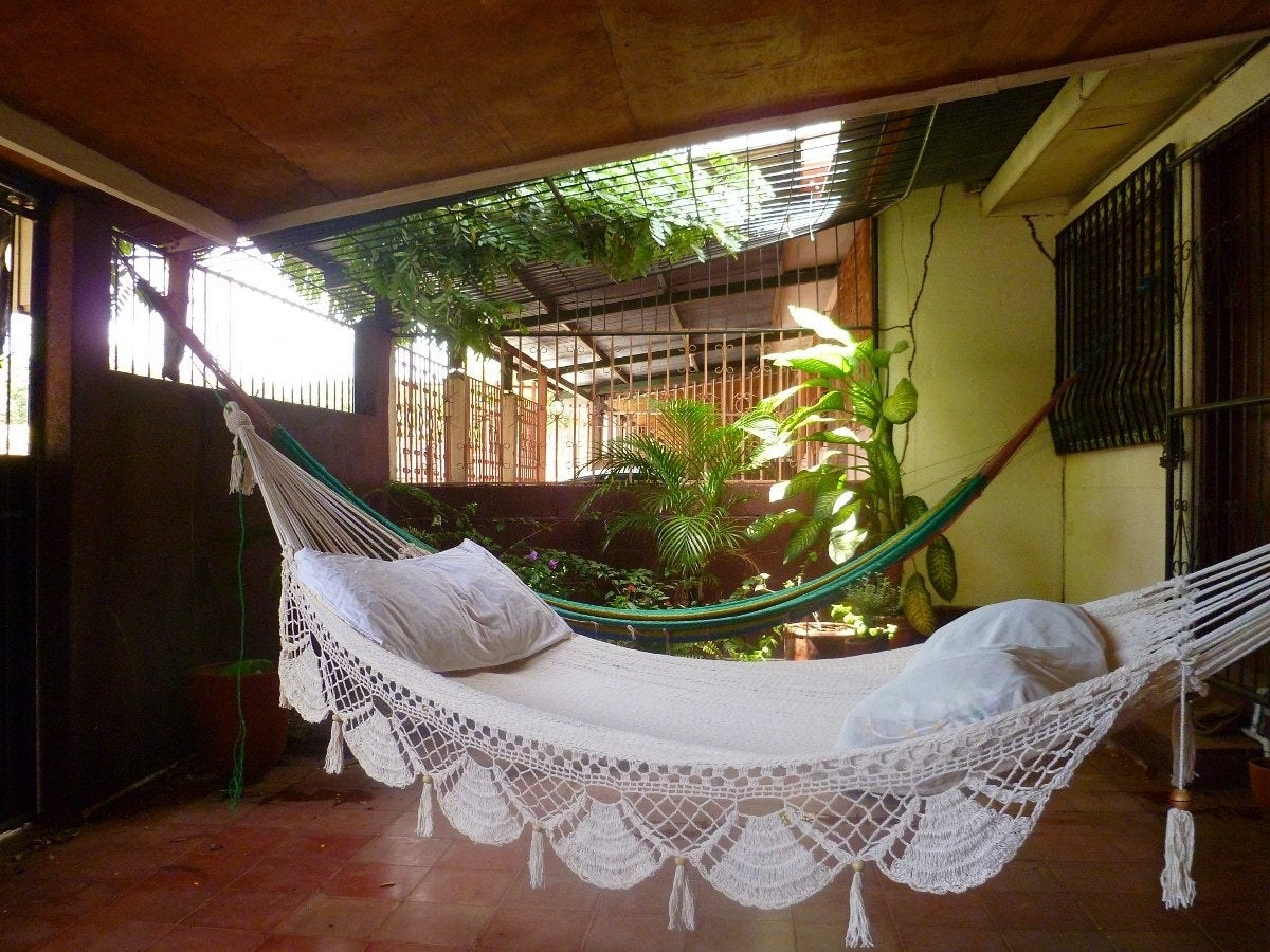 White macrame hammock hanging on green-filled patio
