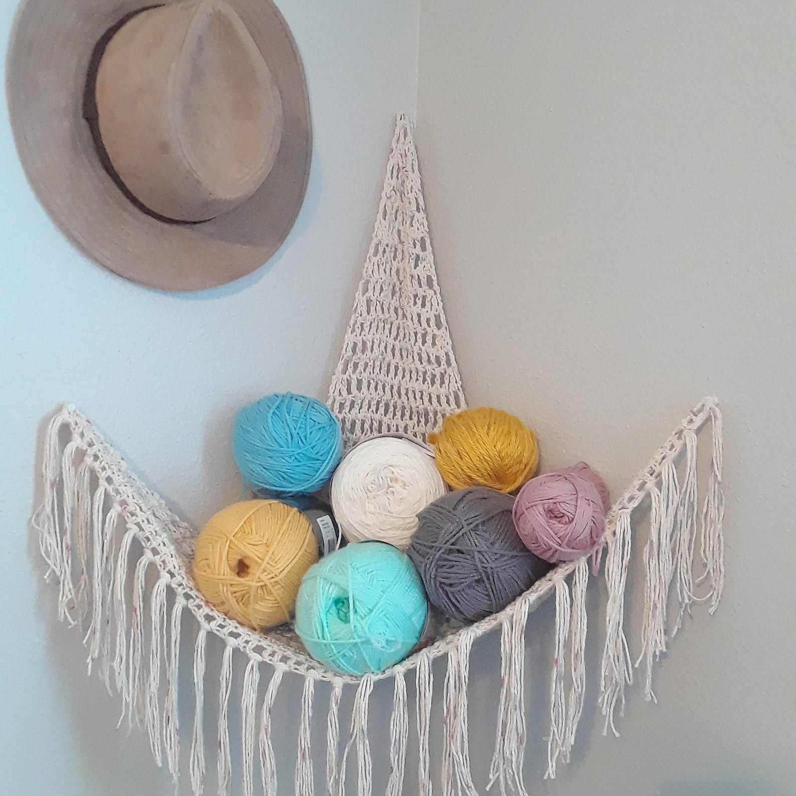 crocheted triangle with fringe attached to a wall corner holding several balls of yarn