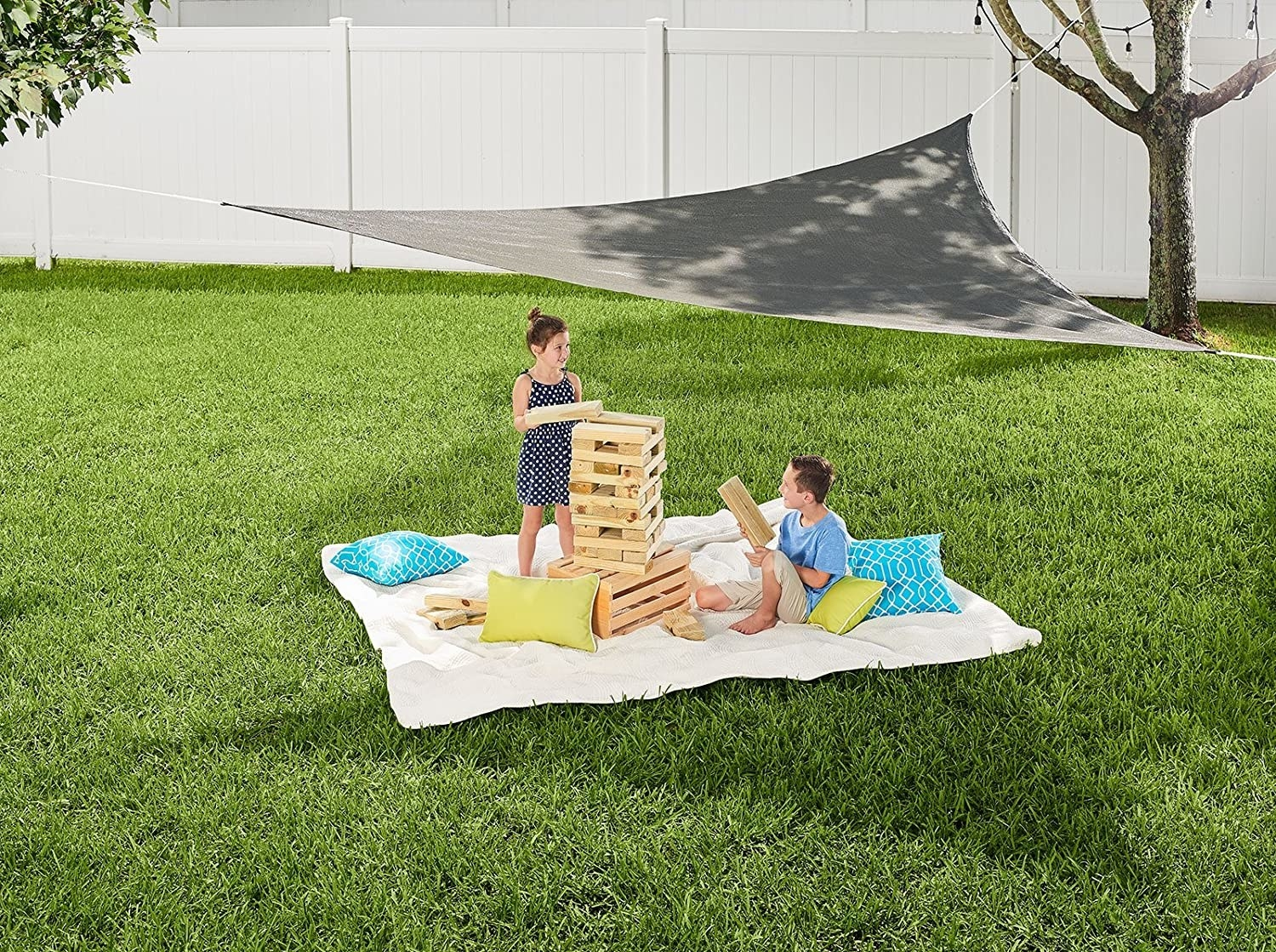 Two kids sitting on the grass with a shade over them