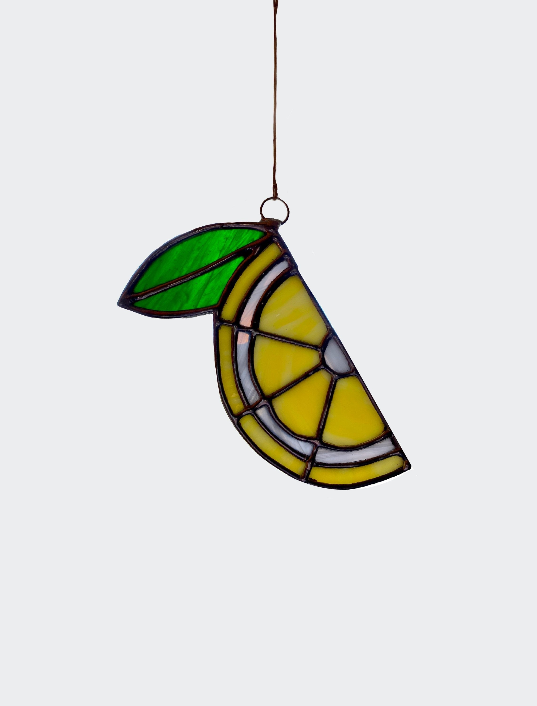 Lemon stained glass sun catcher against grey backdrop