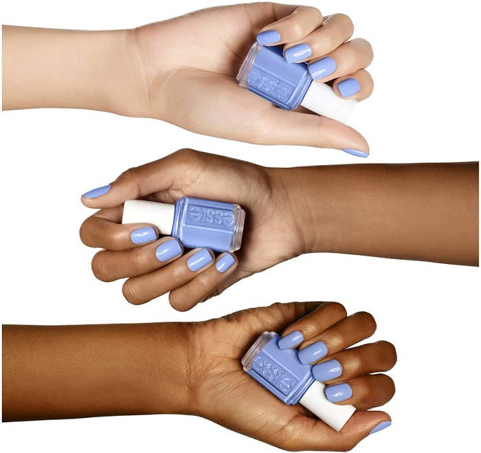 Three hands holding a nail polish with nails painted