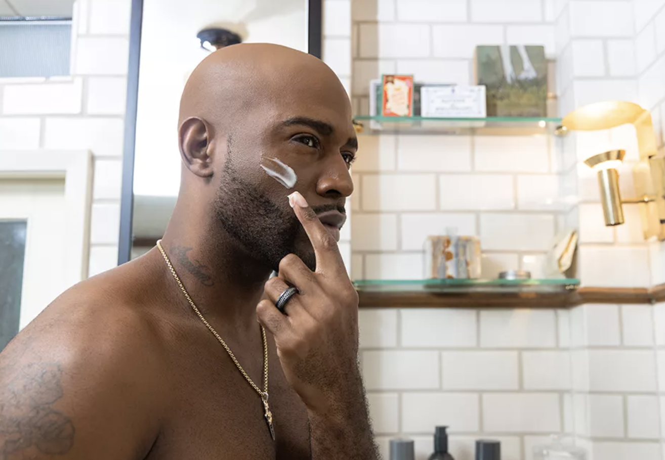 """Karamo Brown from """"Queer Eye"""" applying lotion to his skin in a bathroom"""