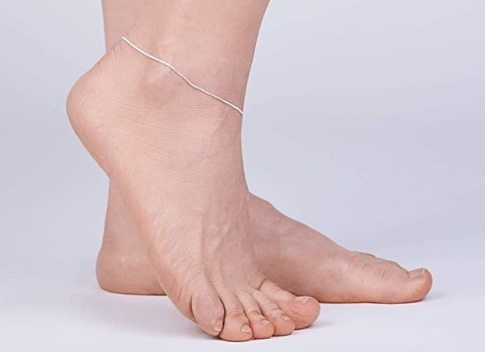 Two feet, one of which has a thin silver anklet