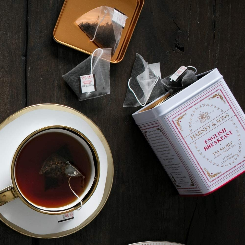 An overhead view of an open tin of tea and tea in a cup