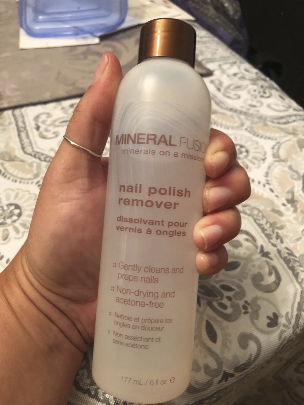 """A reviewer's hand holding a bottle of the remover. It has the brand name """"Mineral Fusion"""" on it."""