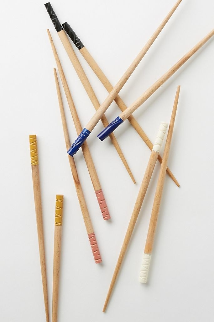Five pairs of bamboo, reusable chopsticks in five different colors.