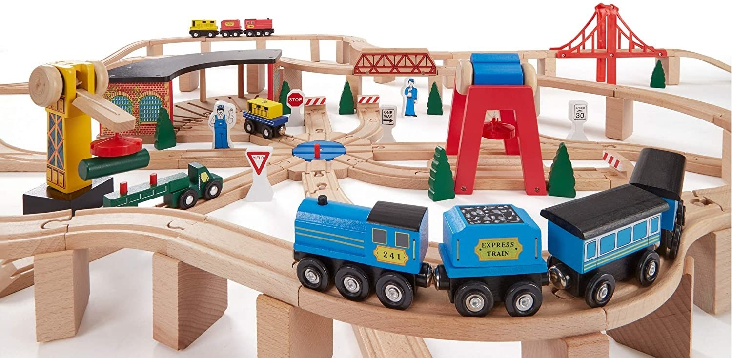 A wooden railway toy set with colorful trains, trucks, a crane, and bridges