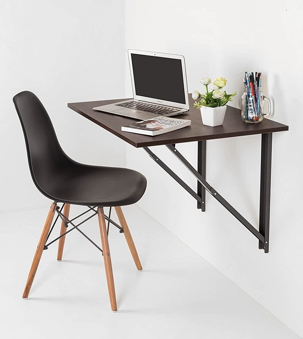 A chair in front of a floating table that's attached to a wall with a laptop and stationery on it