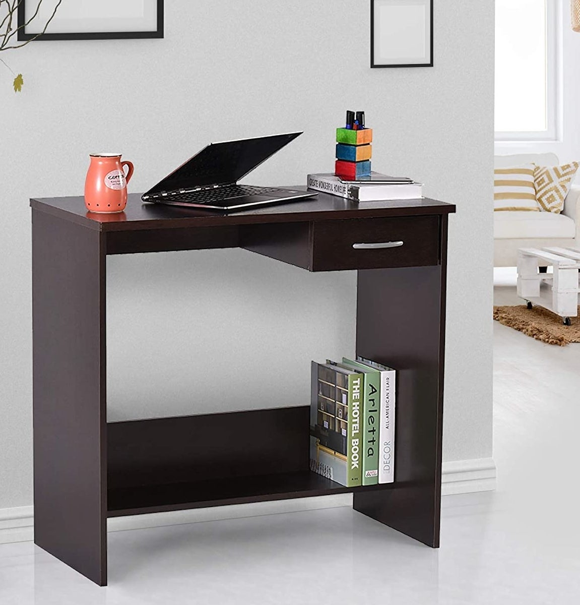 A room with a desk that has a laptop, stationery, and books on it