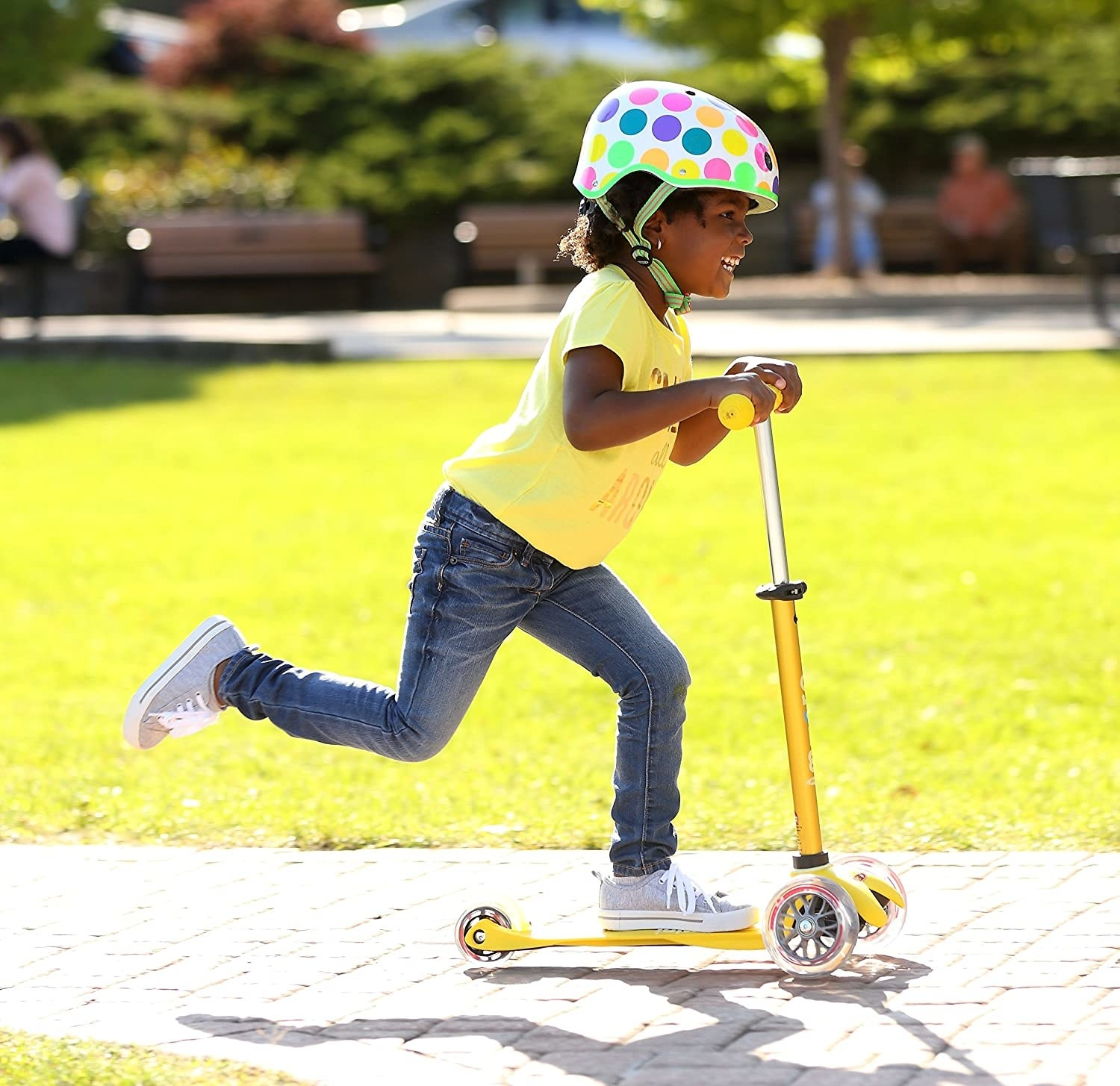 A child model riding a three-wheel scooter outdoors while wearing a helmet