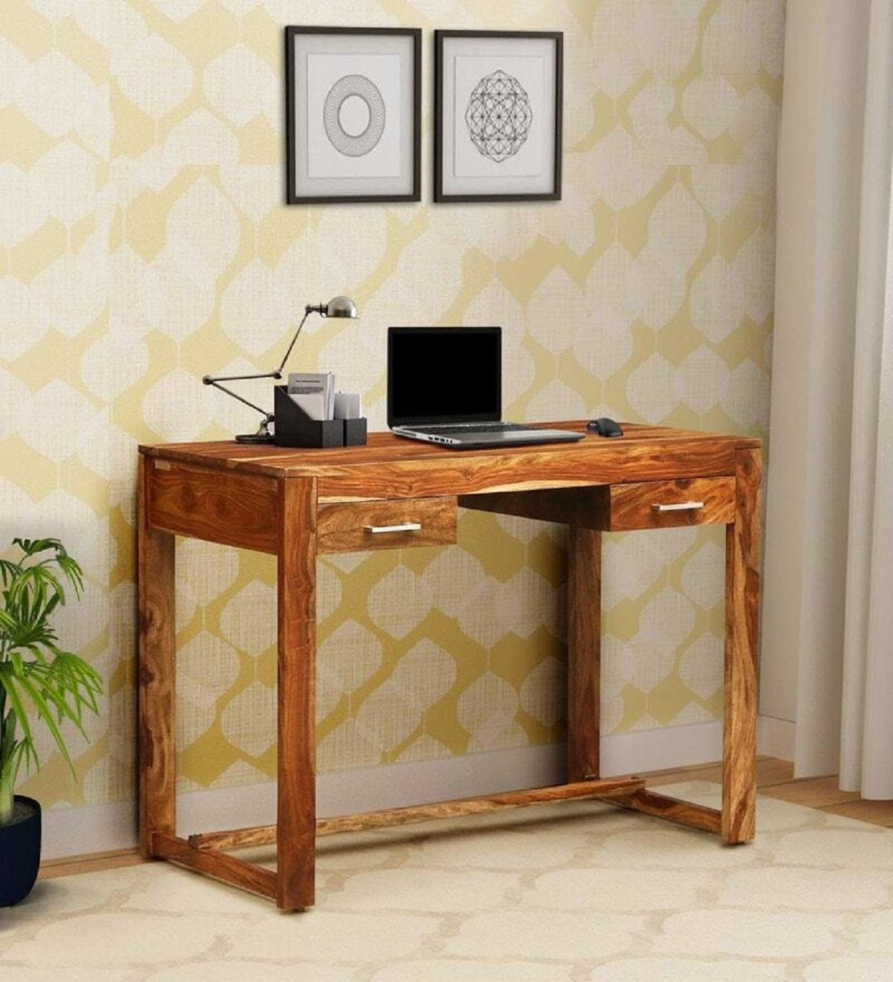 A room with a wooden desk that has a laptop and stationery on it