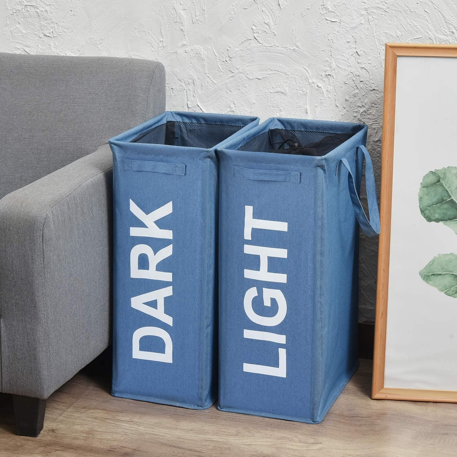 """Laundry hampers labelled """"Dark"""" and """"Light"""" beside a sofa"""