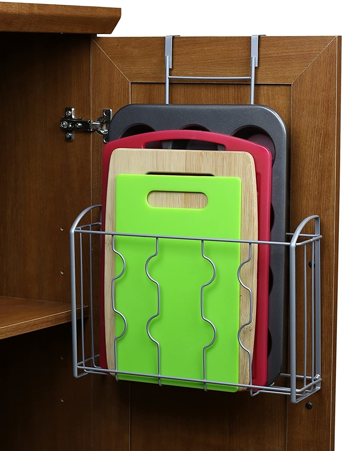 The cabinet organizer hooked onto the back of a cupboard door, holding cutting boards and a muffin tin