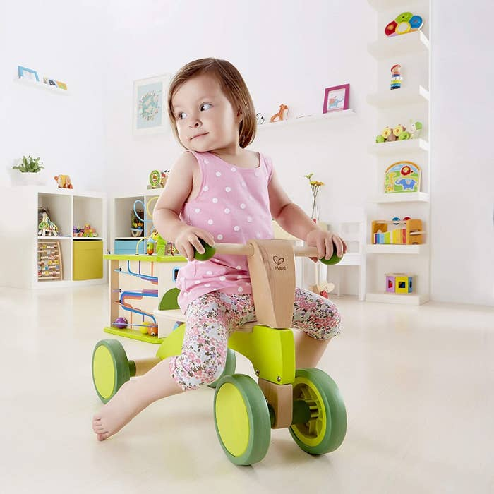 Model child riding a wooden scooter bike with lime green accents on wheels, handle, and base