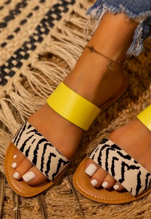 Model wearing sandals with two straps — one bright yellow and the other with a zebra print