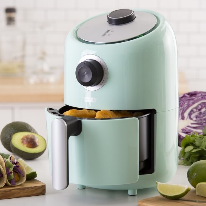 The fryer in mint green, with the drawer (which has a large handle) pulled out to show it cooking chicken nuggets. It has control knobs on the front and top