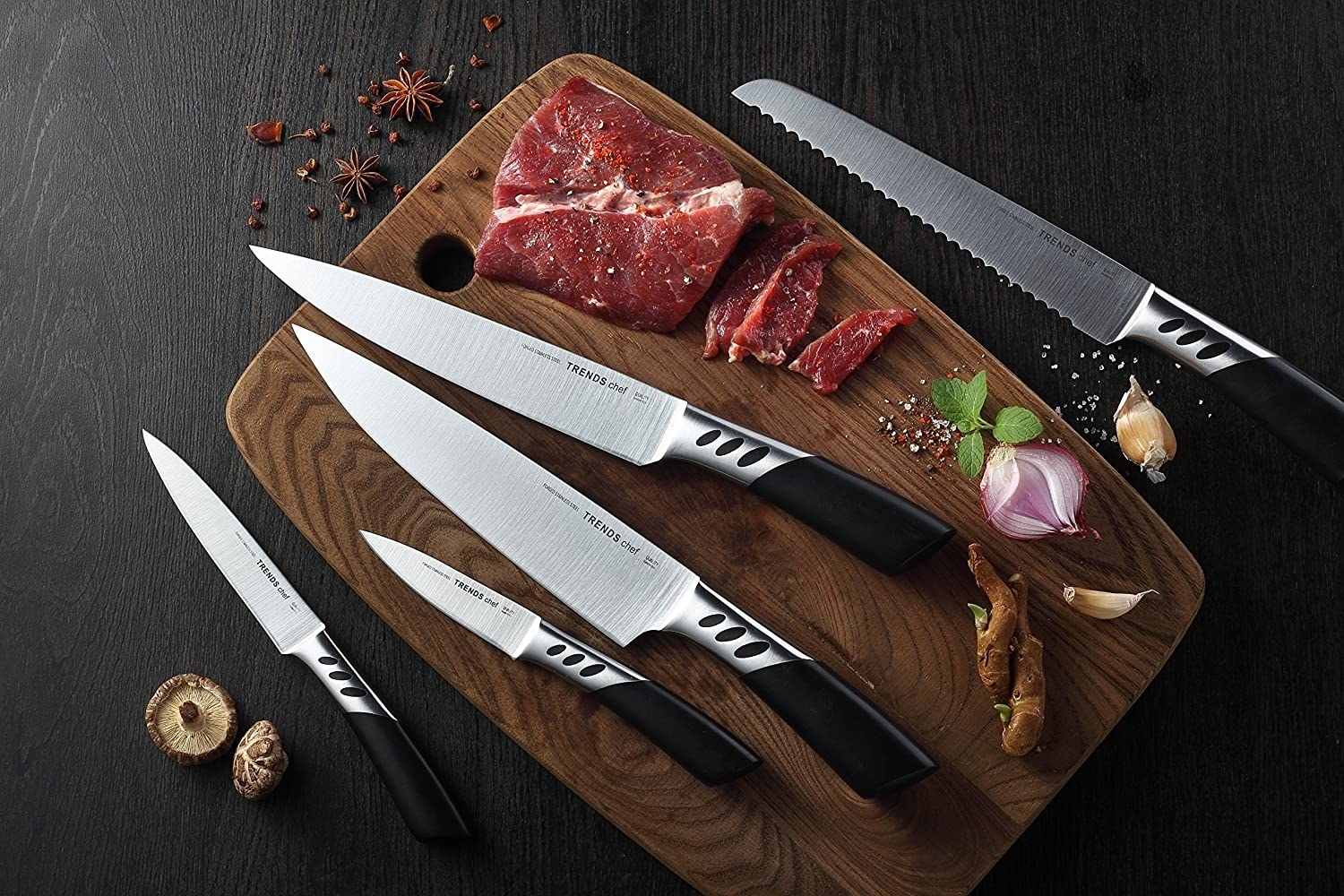 The five knives laying on a cutting board with steak, garlic, mushrooms, and spices