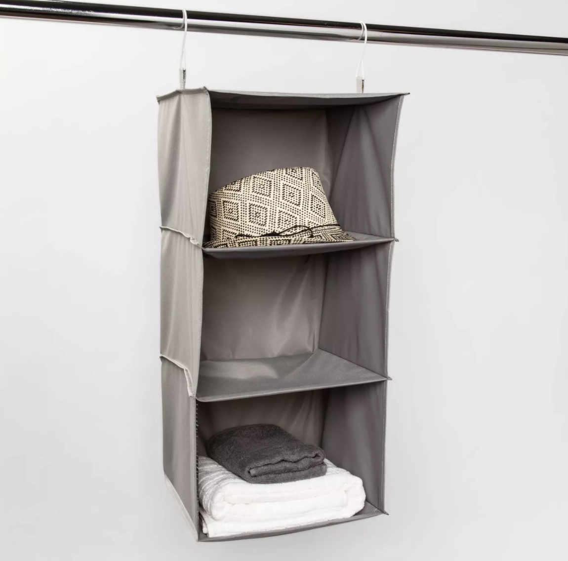 Gray three-shelf hanging organizer with a patterned fedora and folded towels
