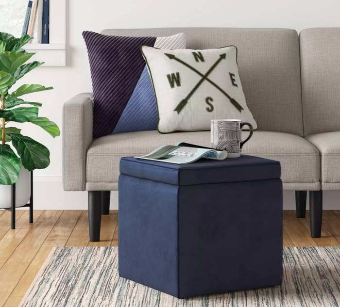 Blue ottoman in living room with coffee mug and magazine on top