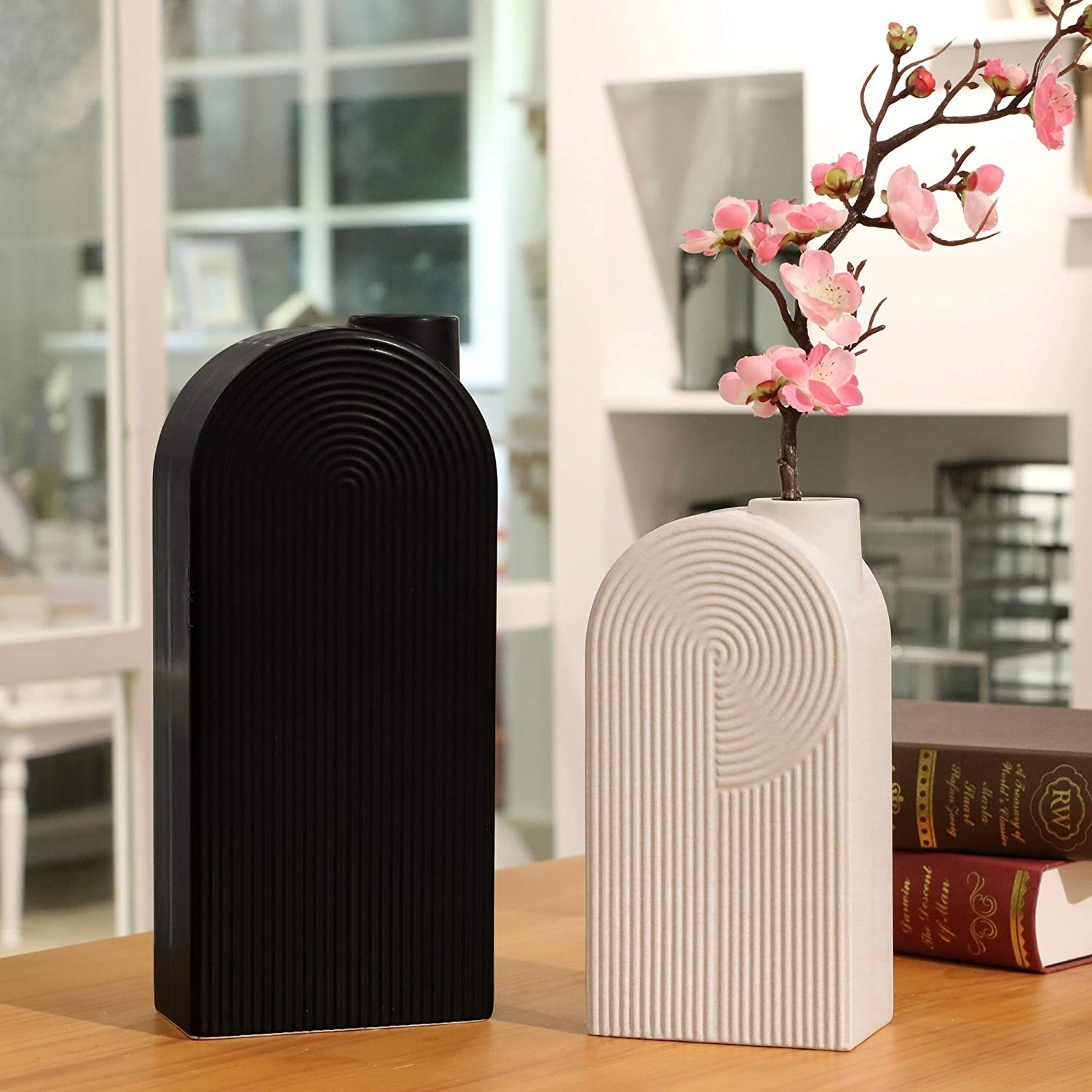 Two vases — one taller black with semi-circular and straight stripes in black and a smaller one with the same design in white