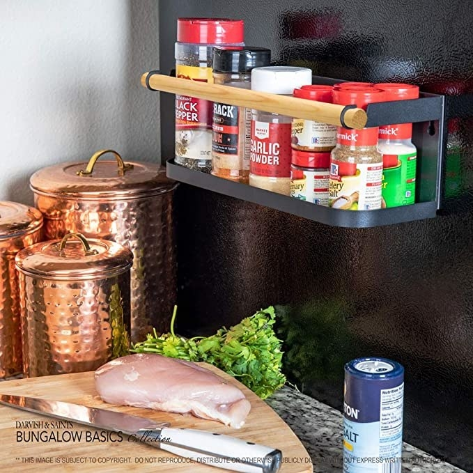 The rack with a wood rod on the side of a fridge with assorted spices in it