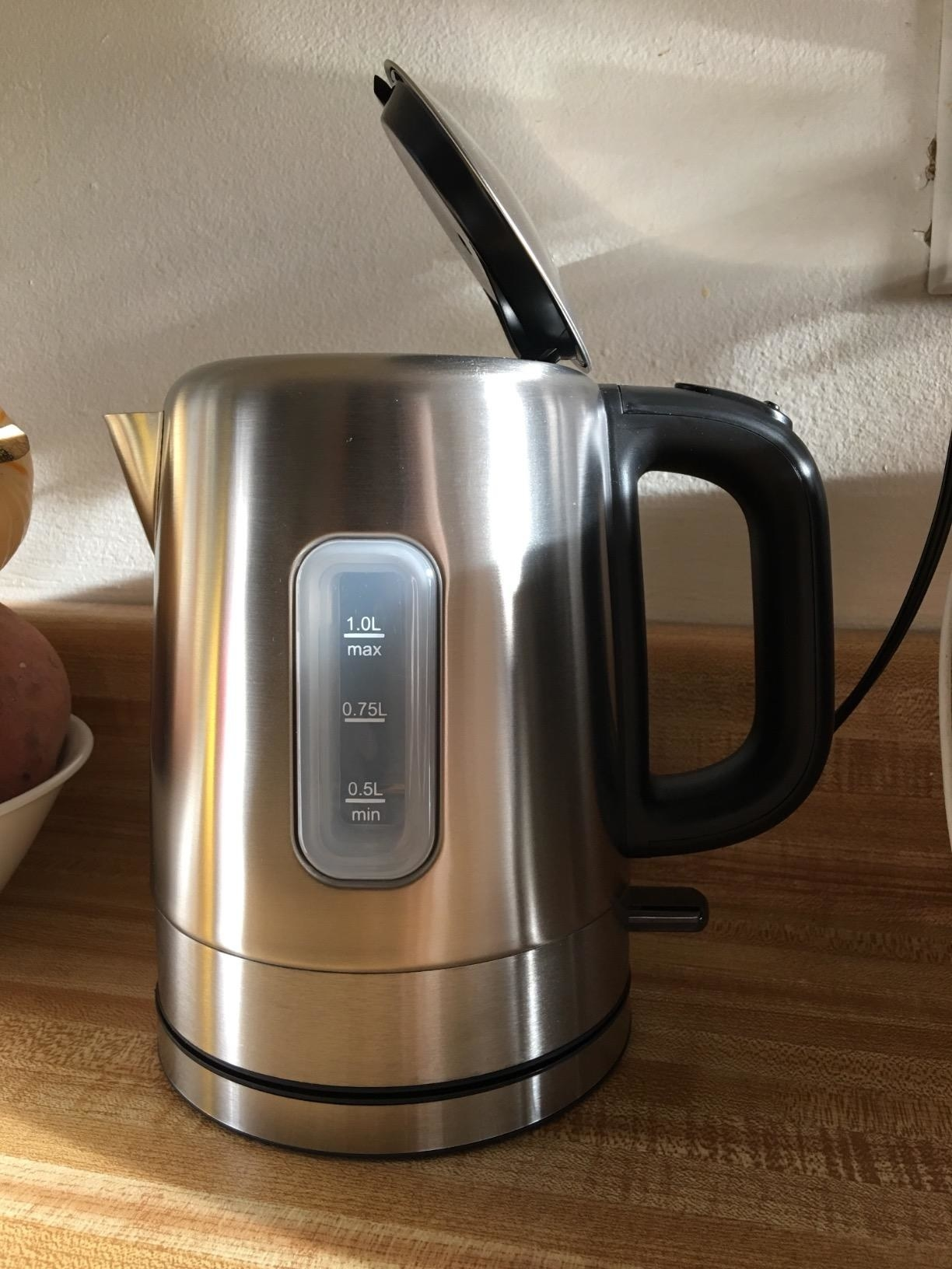 A metallic electric kettle with a black handle and measurements on the side plastic window