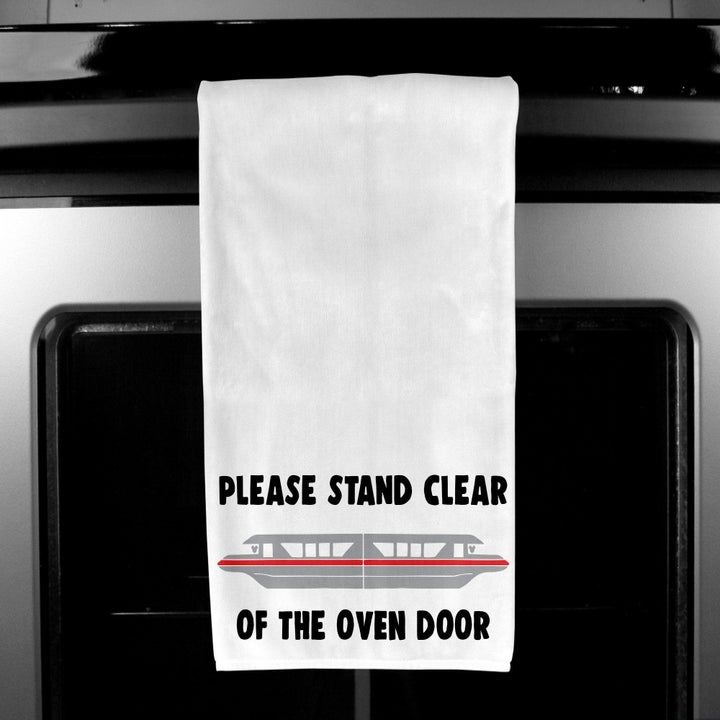 "a white kitchen towel with a design of the monorail on it and the words ""please stand clear of the oven door"" on it in black"