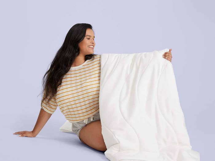 model holds up the comforter