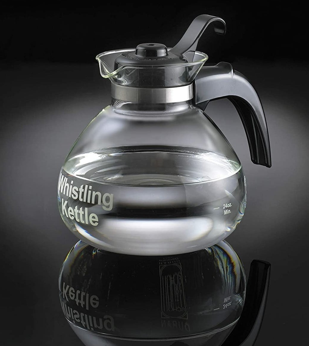 "A glass tea kettle with a black handle that was the words ""Whistling Kettle"" printed on its base"