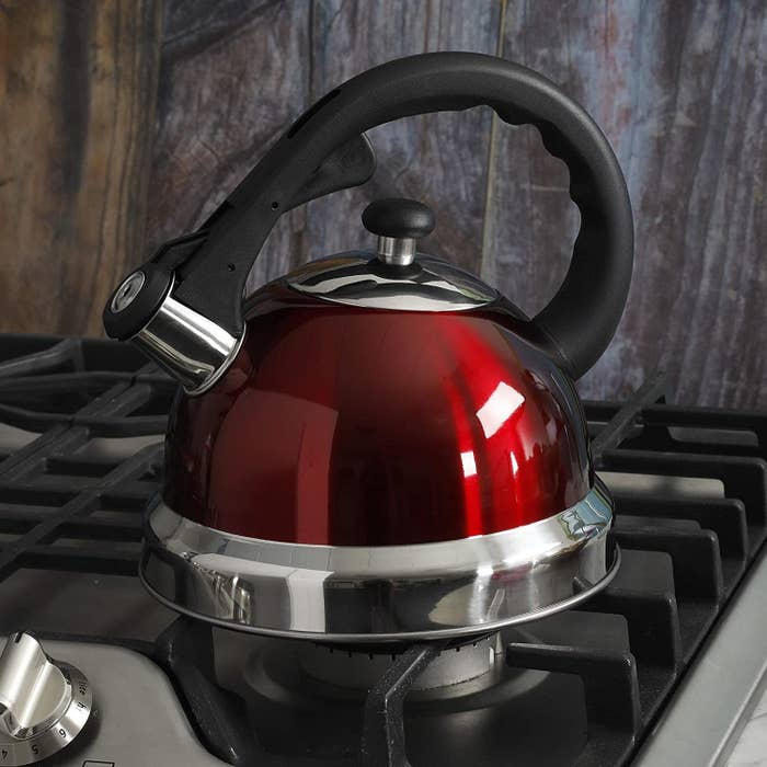 A dark shiny red metallic kettle with a metallic base, spout, lid, and a black handle