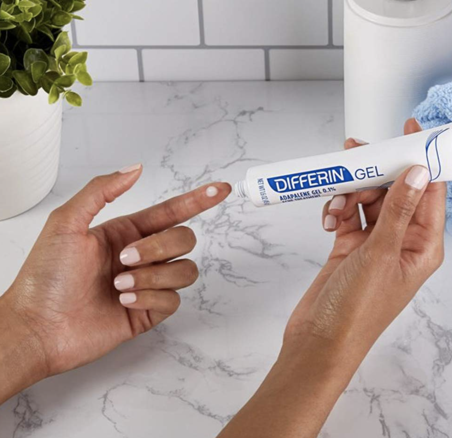 Model applies Differin's Adapalene Gel 0.1% Acne Treatment on their hand