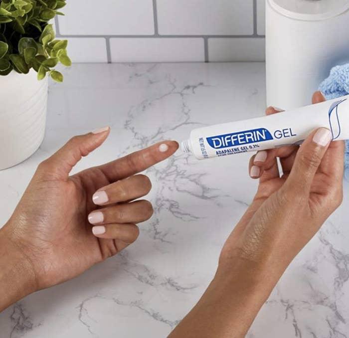 Model applies Differin's Adapalene Gel 0.1% Acne Treatment on their hand