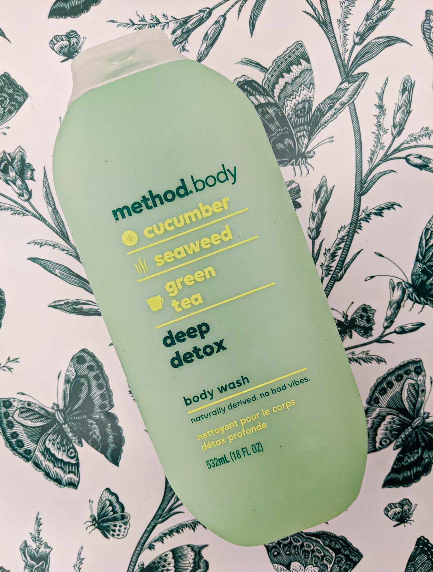 The bottle of body wash against a botanical background with cucumber, seaweed, and green tea listed as ingredients
