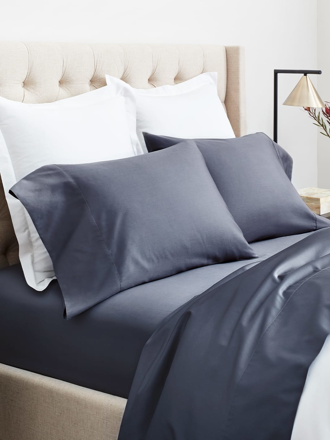 The sheet set in dark blue/gray on a bed