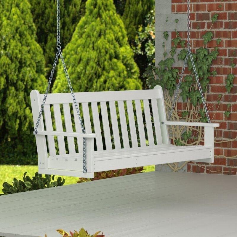A white porch swing hovering above ground
