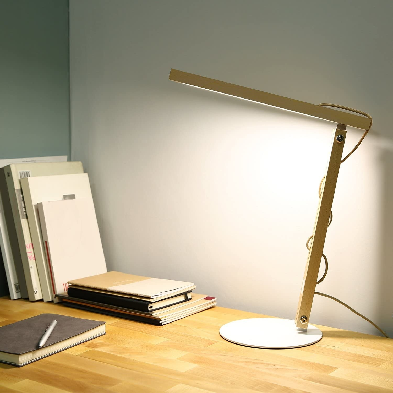 Wooded desk lamp with white circular base and cord running through the arm