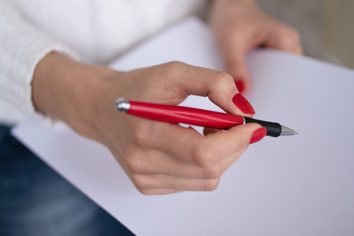 woman holding a red pen